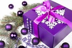 Purplegift ask med julbollar Arkivfoto