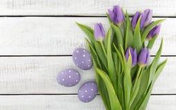 purpleviolet郁金香和被绘的复活节彩蛋花束在丝毫 库存照片
