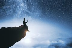 Purpose and success concept. Black backlit young guy silhouette sitting on cliff edge and starry night sky cosmos background. Purpose and success concept stock image