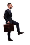 Purposeful businessman comes up with a briefcase Stock Images