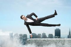 Businessman easily hangs on one finger. Purposeful and confident businessman easily hangs on one finger on the top of skyscraper, cityscape on background Royalty Free Stock Images