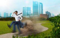 Businessman runs to victory, blur repeating effect. Purposeful and confident businessman runs the way to victory, legs with blur repeating effect, cityscape on Stock Photos