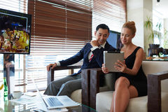 Purposeful man and woman entrepreneurs watching something on touch pad during prepare for conference Stock Photo