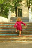 Purposeful toddler girl in pink dress reaching the top of old blue vintage stairs. Outdoors stock photography