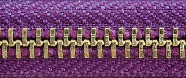 Purpur und geschlossene Schwergängigkeit des Goldreißverschlusses fest zusammen zwei Schichten des Gewebegewebes unter hoher line lizenzfreies stockbild