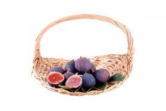 Purpura figs i en sugrörkorg Arkivfoton