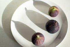 Purpura figs på en vit platta Arkivfoton