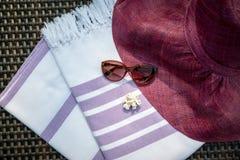 Purpura i biel barwimy Turecki peshtemal, ręcznika, okulary przeciwsłonecznych, białych seashells i słomianego kapelusz na rattan zdjęcia stock