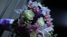 Purpure e ramalhete branco do casamento fora em um banco de madeira filme