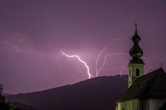 Purpurfärgad blixtstorm med kyrkan i förgrund Arkivbild