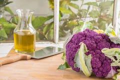 Purpurfärgad blomkål och karaff av olivolja Arkivfoto