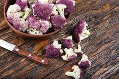 Purpurfärgad blomkål på en träbakgrund Royaltyfri Bild
