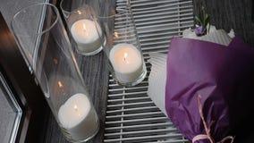 Purpurfärgad bukett av blommor och stearinljus som en gifta sig garnering close upp stock video