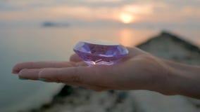 Purpurfärgad diamantkristall i en kvinnlig hand, slut upp, på solnedgångbakgrund lager videofilmer