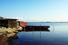 Purpurfärgad fiskebåt i stillsamt vatten royaltyfria foton