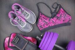 Purpurfärgad hantel, sportbehå och gymnastiksko, sportutrustningar, konditionobjekt, bästa sikt royaltyfria bilder