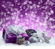 Purpurfärgad jul packe, gåva av ett silverband Klirrklockor, silverjulbollar och pålagd snö för julstjärnor Abstrac Royaltyfria Foton