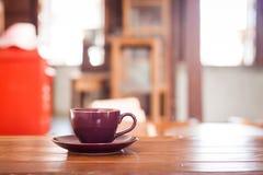 Purpurfärgad kaffekopp på trätabellen Arkivfoto