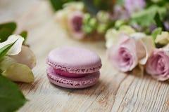 Purpurfärgad makronkaka med rosor på tabellöverkant royaltyfri foto