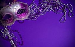 Purpurfärgad Mardi-Gras eller Venetian maskering på purpurfärgad bakgrund Royaltyfri Foto