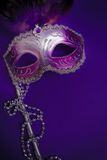 Purpurfärgad Mardi-Gras eller Venetian maskering på purpurfärgad bakgrund Royaltyfri Fotografi