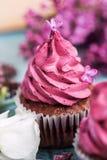 Purpurfärgad muffin med virvel, purpurfärgad lila på blåtttabellen Royaltyfri Fotografi