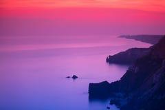 Purpurfärgad och rosa solnedgång över havet Arkivfoton