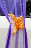 Purpurfärgad Organza och orange pilbåge på en vit bröllopbil Arkivbild