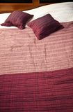 Purpurfärgad sängräkning och kuddar Arkivfoto