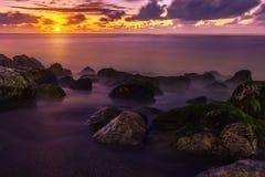 Purpurfärgad solnedgång över havskust Arkivbilder