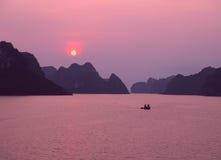 Purpurfärgad solnedgång i den Halong fjärden Royaltyfria Bilder