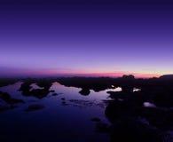 Purpurfärgad solnedgång och sjösida Arkivfoton