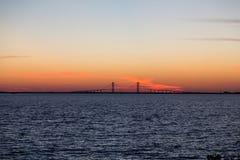 Purpurfärgad solnedgång och upphängningbro Royaltyfria Bilder