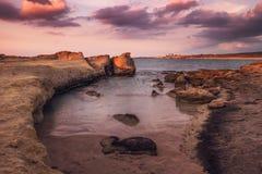 Purpurfärgad solnedgång på ökenkustlinjen på nordliga Cypern Royaltyfria Foton