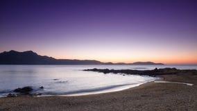 Purpurfärgad solnedgång på den Arinella plagen i Korsika Fotografering för Bildbyråer
