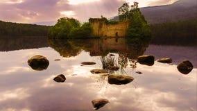 Purpurfärgad solnedgång på sjön med en slott Arkivbilder