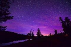 Purpurfärgad Stary natthimmel över skog och sjön Arkivbilder