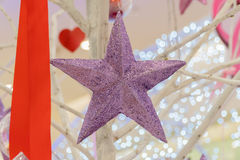 Purpurfärgad stjärna som dekorerar ett julträd Royaltyfri Fotografi
