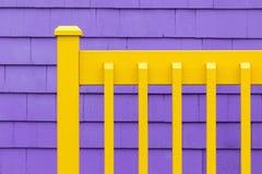Purpurfärgad vägg och gult staket Royaltyfria Bilder