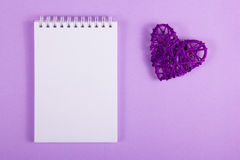 Purpurfärgad valentin och öppen anteckningsbok med tomma sidor på en purpurfärgad bakgrund Arkivbild