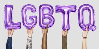 Purpurfärgade alfabetballonger som bildar ordet LGBTQ royaltyfria bilder