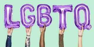 Purpurfärgade alfabetballonger som bildar ordet LGBTQ royaltyfri fotografi