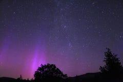 Purpurfärgade Aurora Borealis eller nordliga ljus med Vintergatan arkivbild