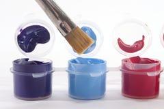 Purpurfärgade blåa röda akrylmålarfärger och målarpensel Arkivbilder