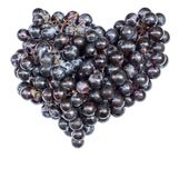 Purpurfärgade druvor i formen av hjärtanärbilden som isoleras på vit bakgrund arkivfoton
