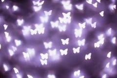 Purpurfärgade fjärilsbokehljus Bokeh defocused bakgrund arkivfoto