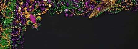 Purpurfärgade, guld- och gröna Mardi Gras pärlor och garneringar arkivbild