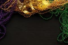 Purpurfärgade, guld- och gröna Mardi Gras pärlor och maskering royaltyfri fotografi