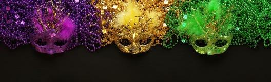 Purpurfärgade, guld- och gröna Mardi Gras pärlor och maskeringar royaltyfria bilder