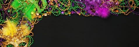 Purpurfärgade, guld- och gröna Mardi Gras pärlor och maskeringar royaltyfri bild